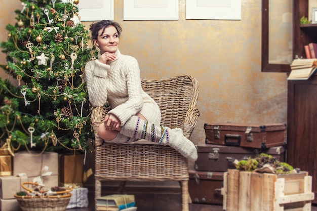 크리스마스 인테리어에 베개가 있는 의자에 앉아 휴식을 취하는 아름다운 여성