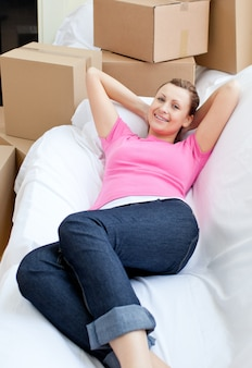 Beautiful woman relaxing on a sofa with boxes