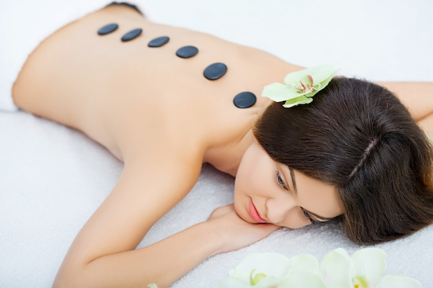 Beautiful woman relaxing in spa salon with hot stones on body
