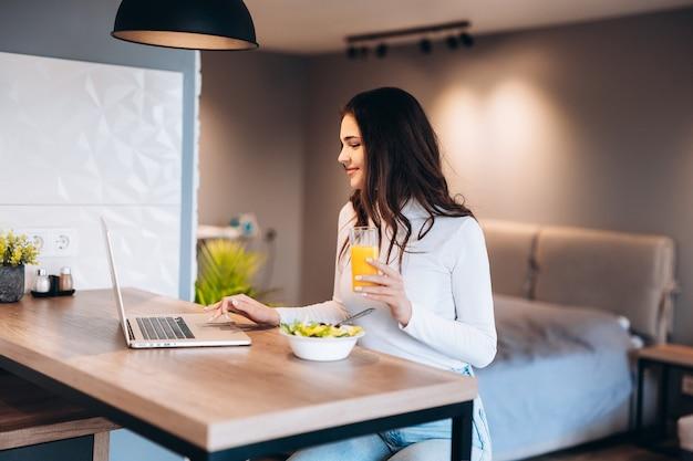 キッチンでオレンジジュースのガラスを保持しながら彼女のラップトップでリラックスした美しい女性。検疫封鎖で自宅で仕事をしています。社会的距離の自己隔離。