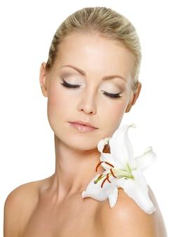 흰색 절연 그녀의 몸에 흰 백합과 함께 편안한 아름 다운 여자