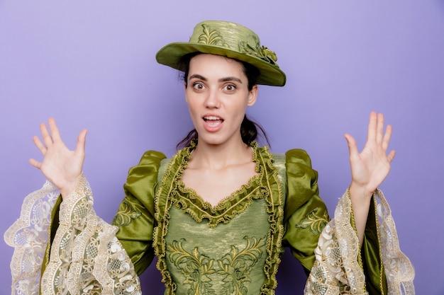 Bella donna in abito rinascimentale e cappello felice ed eccitata che alza le palme in segno di resa sul blu