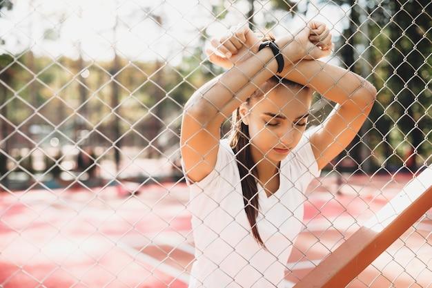 スポーツパークで屋外の朝の有酸素運動をした後に休んでいる美しい女性。