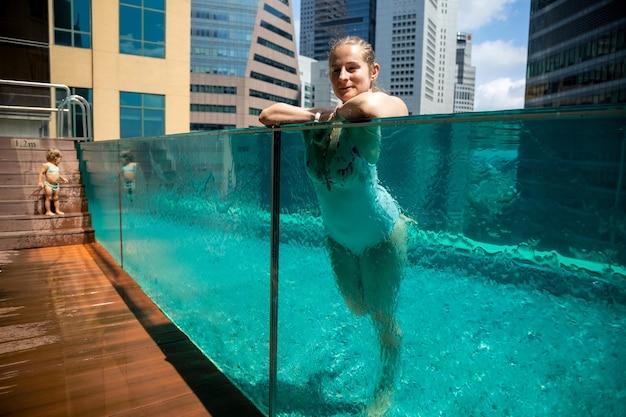 Красивая женщина отдыхает в бассейне на фоне городского пейзажа