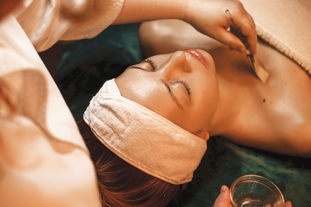 Красивая женщина отдыхает во время процедур по уходу за кожей в оздоровительном спа-салоне.