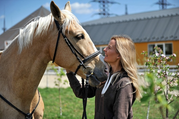 Beautiful woman rider jockey having fun with her favorite horse. tenderness, love and animals concept.