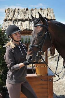 Beautiful woman rider jockey having fun with her favorite horse.