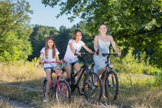Beautiful woman riding with daughters on bicycles at field