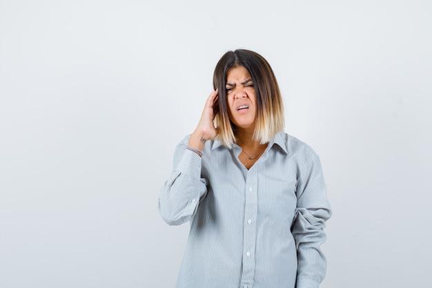 こめかみをこすり、シャツに頭痛を感じ、苦しんでいるように見える美しい女性、正面図。