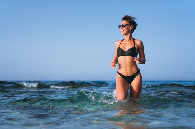Beautiful woman running out of the ocean