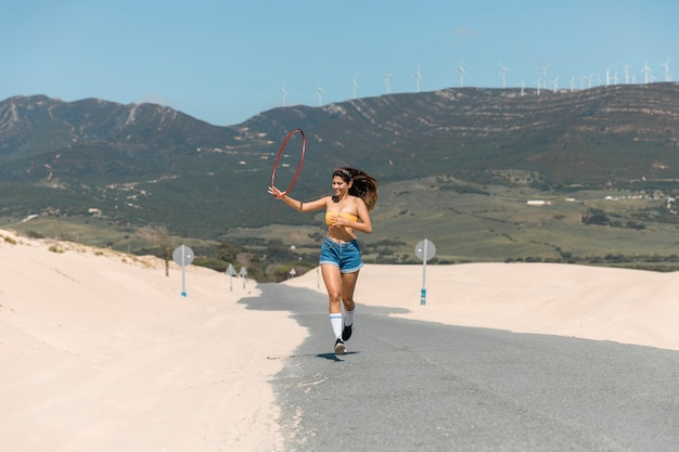 Beautiful woman running with hula hoop on sand
