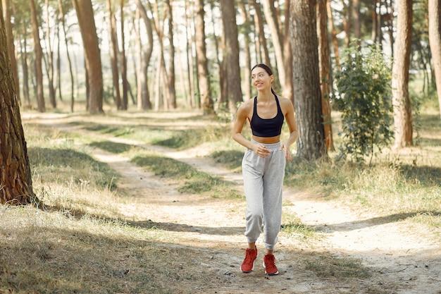 Красивая женщина бежит в летний парк
