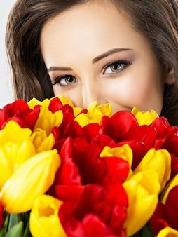 꽃 사이에서 아름 다운 여자의 눈. 매력적인 여자의 초상화는 빨간색과 노란색 튤립으로 얼굴을 커버