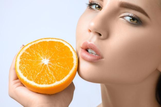 Лицо красивой женщины с вкусным апельсином в студии