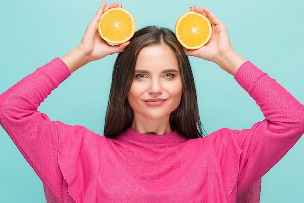 Beautiful woman's face with delicious orange at