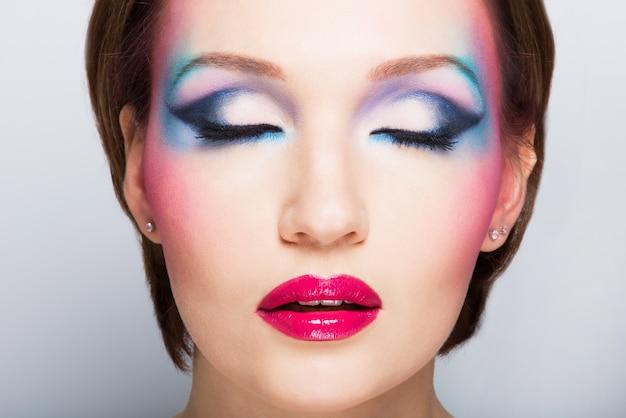 Лицо красивой женщины с ярким макияжем моды. фронтальный портрет с закрытыми глазами