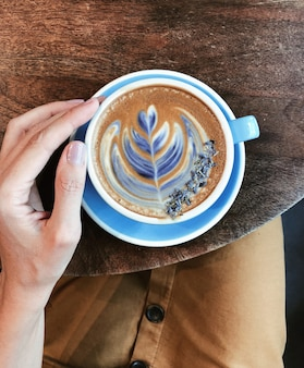 Beautiful woman's hand holding a big blue mug with coffee. top view on drawing on coffee foam. concept of a cozy and beautiful breakfast