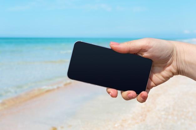 Beautiful woman's hand using smart phone at beach