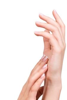 Руки красивой женщины с красивыми ногтями после маникюрного салона с французским маникюром