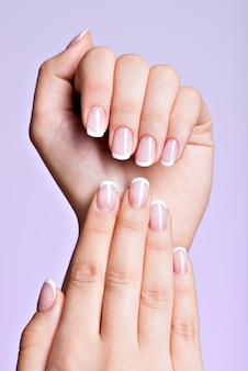 フレンチマニキュアのマニキュアサロンの後の美しい爪を持つ美しい女性の手