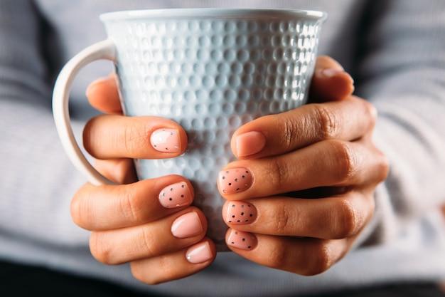 Руки красивой женщины с розовыми гвоздями на белом фоне. лакировка ногтей розовым цветом. маникюр, концепция салона красоты педикюра.