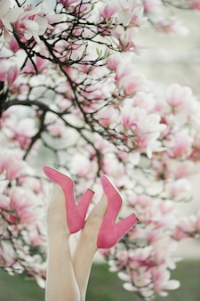 Beautiful woman's legs in the pink shoes on the blossom magnolia tree