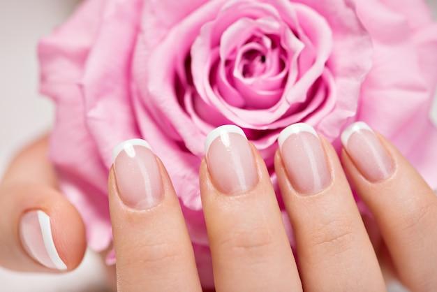 Ногти красивой женщины с красивым французским маникюром и розовой розой