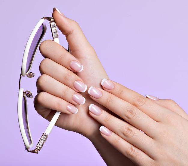 아름 다운 프랑스 흰색 매니큐어와 아름 다운 여자의 손톱