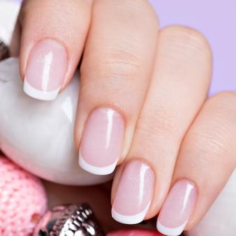 Le unghie della bella donna con una bella manicure bianca francese