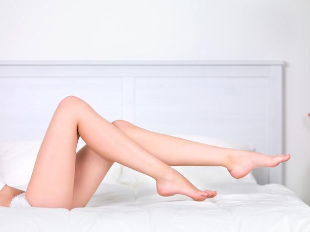 ベッドの上の美しい女性の完璧なきれいな脚-屋内