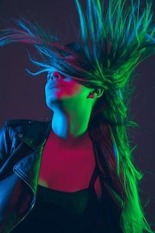 Ritratto di bella donna con i capelli che soffia in luce al neon colorato