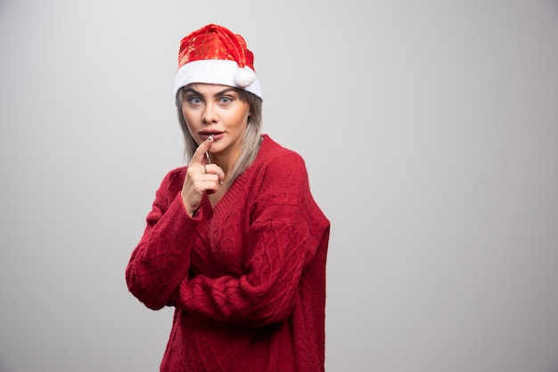 Beautiful woman in santa hat looking at camera.