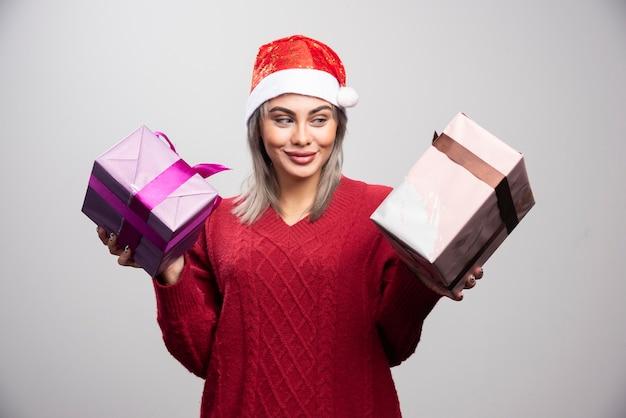 Bella donna in cappello della santa che guarda felicemente i regali di natale.
