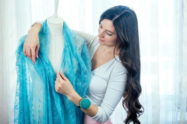 長い黒髪の美しい女性の針子は、マネキンの生地をドレープします。仕立て屋は服の色を選びます。洋裁、ミシン、巻尺、マネキンワークショップで。
