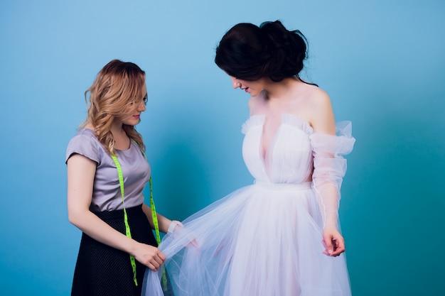 Красивая женщина швея с длинными волосами и клиентом. портной создает образ для клиента в швейной мастерской. портниха измеряет девушку с рулеткой. концепция дизайна одежды