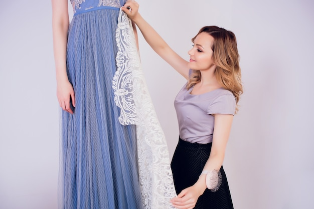 長い髪と顧客の美しい女性仕立て屋。仕立て屋は縫製工場で顧客のためのイメージを作成します。仕立て屋は、測定テープを持つ少女を測定します。コンセプトファッションデザイン