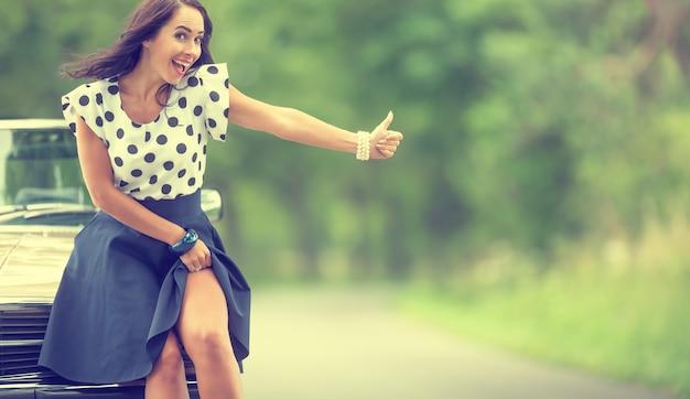 Красивая женщина соблазнительно приподнимает юбку рядом с разбитой машиной, проезжая автостопом, минуя водителей.