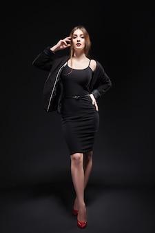 Beautiful woman in sexy evening dress against dark