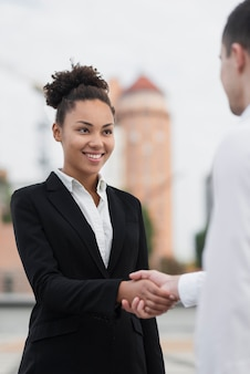 Beautiful woman shaking hands with colleague
