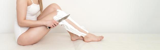 美しい女性は、白い背景にシェービングフォームを塗ったナイフで彼女の足を剃ります。サイトのバナー。スペースをコピーします。