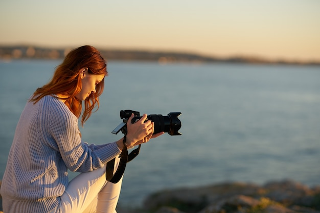 Beautiful woman in a shirt and trousers near the sea with a camera in her hands