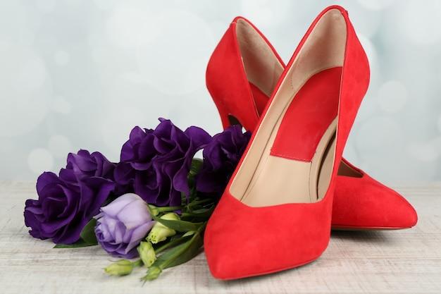 ぼやけたライトに花を持つ美しい女性の靴
