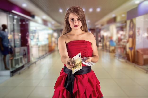 Beautiful woman in shopping centre offer euro
