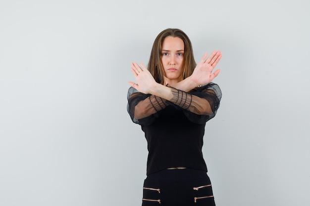 Bella donna che mostra gesto chiuso in camicetta nera e che sembra seria