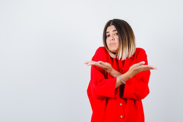 Beautiful woman showing helpless gesture by shrugging in red blouse and looking perplexed . front view.