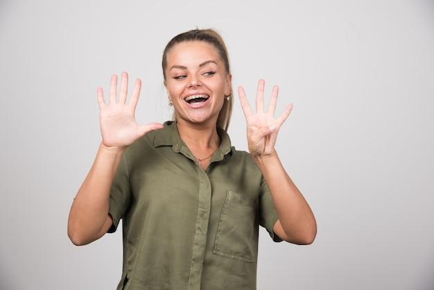 Bella donna che mostra le sue dita sul muro grigio.