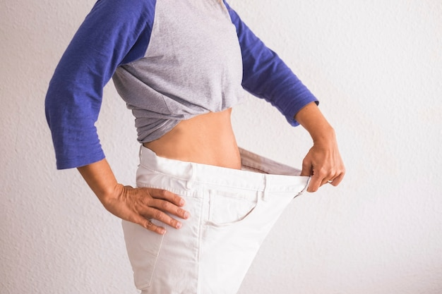 Beautiful woman showing her old big pantalon after losing weight ah home - fitness at home and working to stay better with yourself - eating good