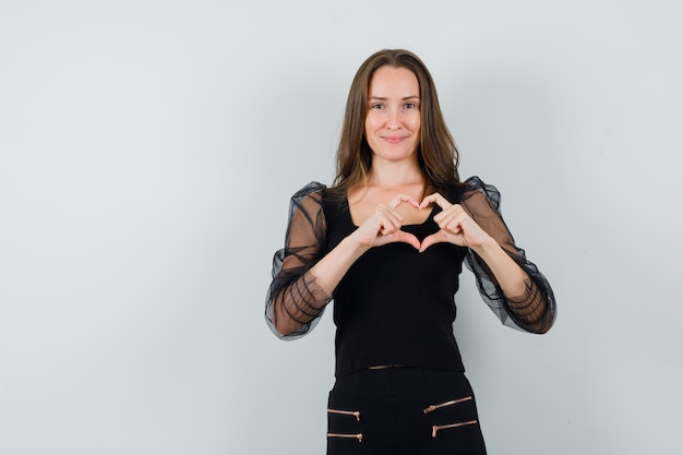 Bella donna che mostra il gesto di pace in camicetta nera e che sembra amata Foto Gratuite
