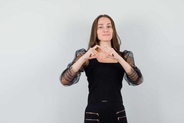 Bella donna che mostra il gesto di pace in camicetta nera e sembra adorabile. vista frontale.