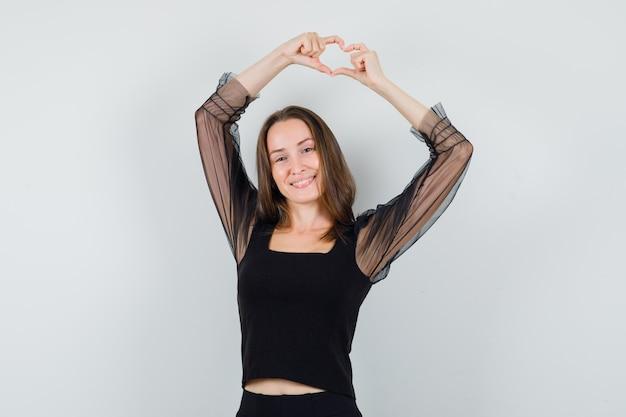 Bella donna che mostra il gesto di pace sopra la sua testa in camicetta nera e sembra allegra